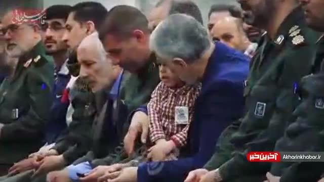 صحنه ای زیبا از گل گرفتن سردار شهید حاج قاسم سلیمانی از فرزند شهید در هنگام نماز